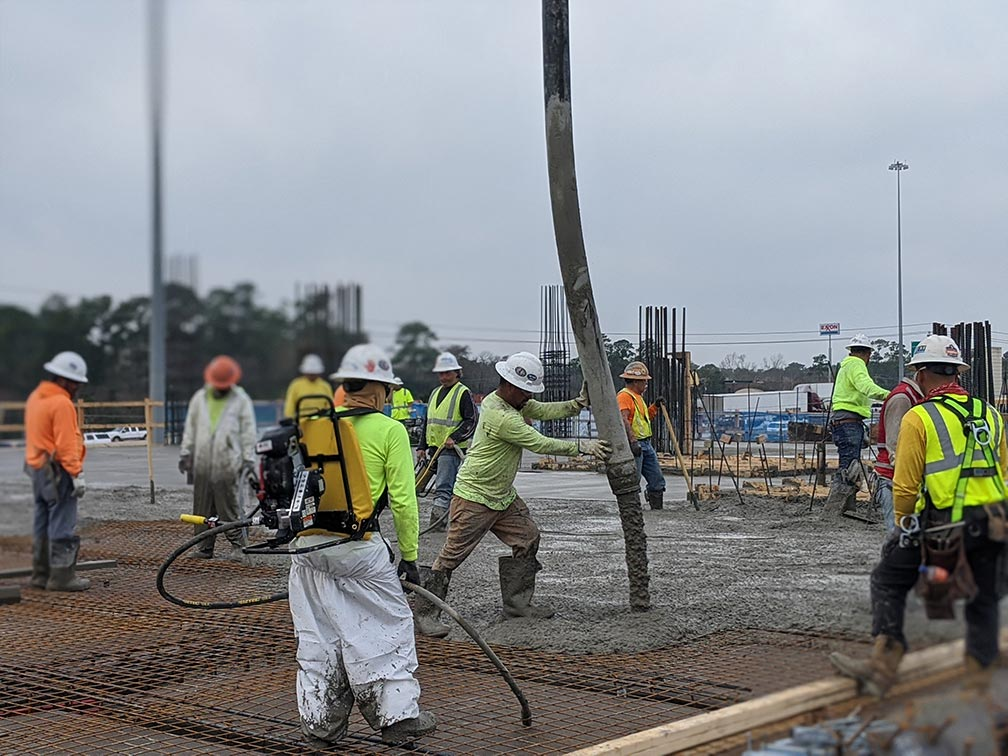 Image of concrete being poured with construction workers standing by